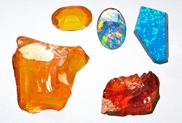 Opaaleja, vasemmalla (kellertävät) tuliopaali, Venäjä. Pyöröhiottu kivi jalo-opaali, Autralia. Oikealla ylhäällä synteettinen opaali, Venäjä. Oikealla alhaalla tuliopaali, Meksiko. (Seppo Lahden kokoelmat). Kuva: Jari Väätäinen, Geologian tutkimuskeskus, 2003